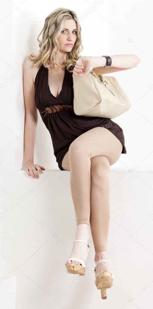 f7835b7c825 Γυναίκα συνεδρίασης που φοράει τα καλοκαιρινά ρούχα και παπούτσια με μια  τσάντα– εικόνα αρχείου