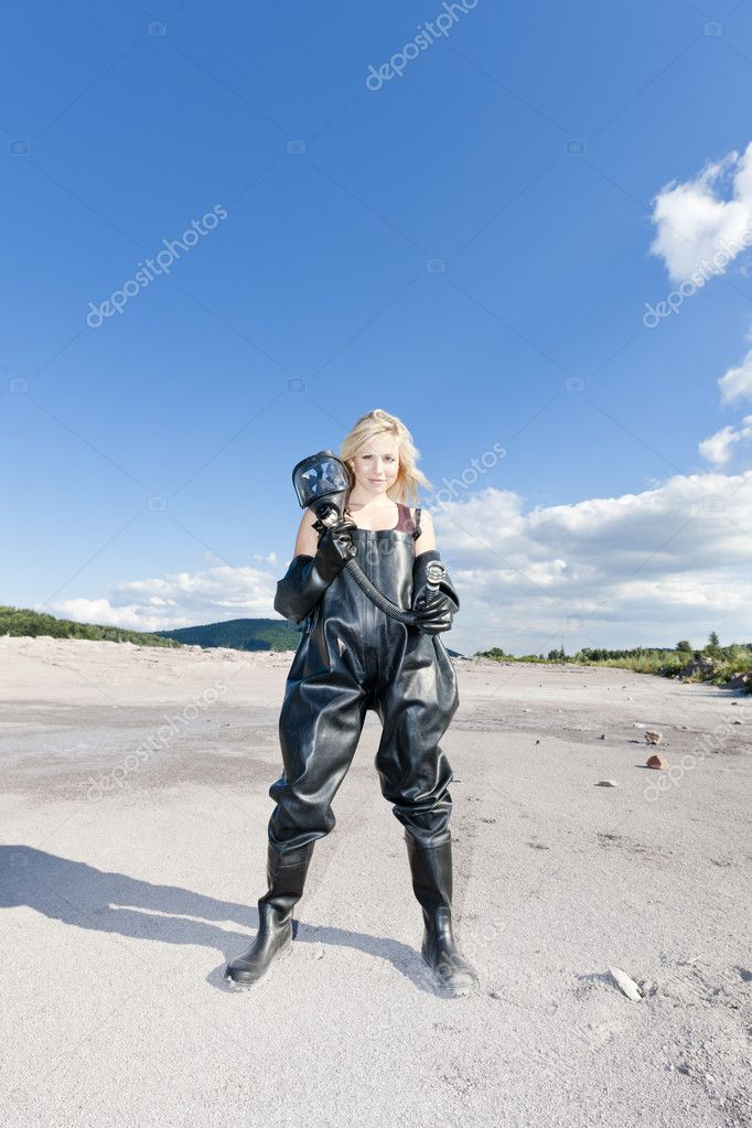 Standing woman with gas mask wearing protective clothes