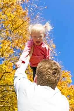 Father with her little daughter in autumnal nature
