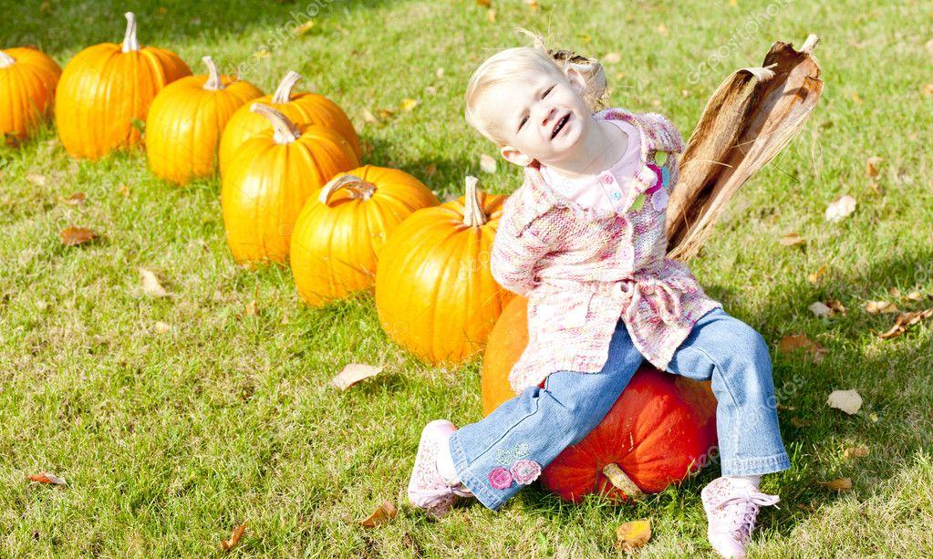 Little girl with pumpkins stock vector