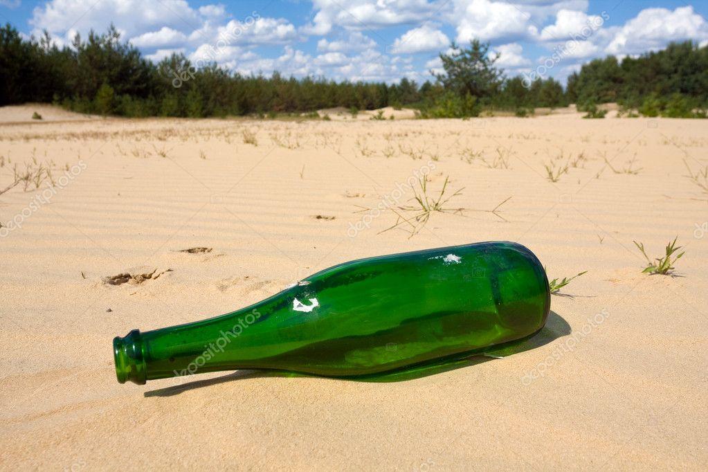 Green bottle in sands