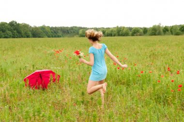 Woman walks through a poppy field
