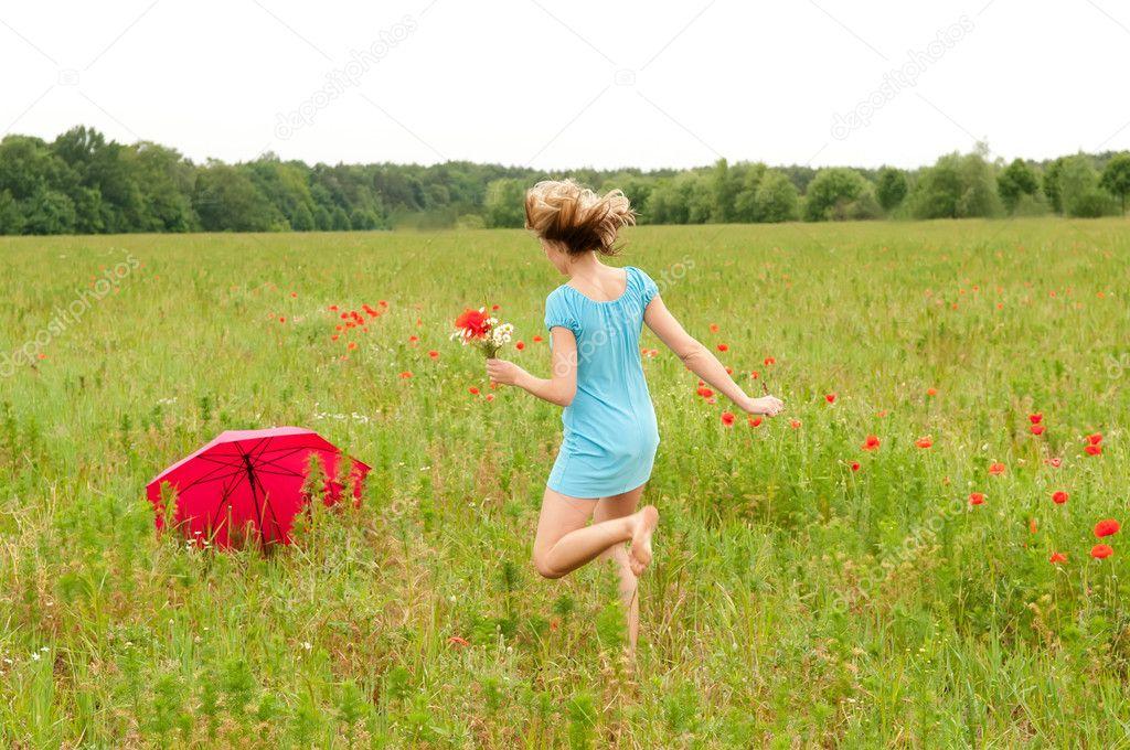 Woman walks through a poppy field