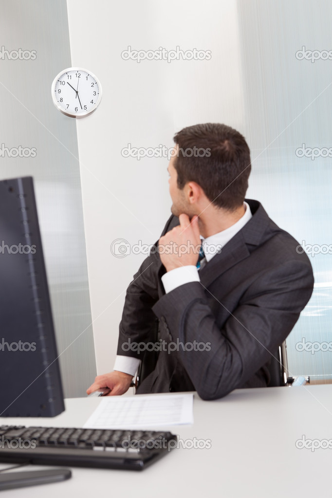 Anxious businessman looking at clock at the office