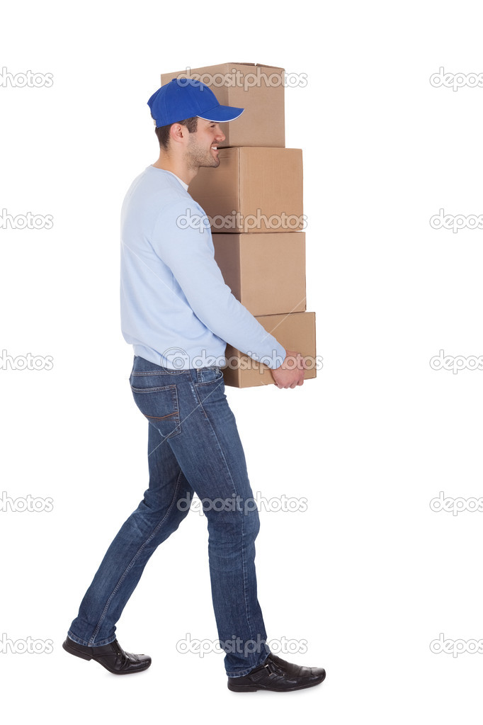 Smiling young delivery man holding stack of boxes. Isolated on white