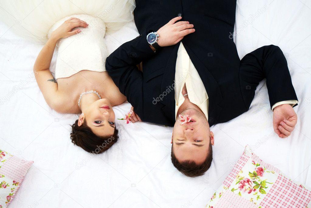 Braut und Bräutigam im Schlafzimmer mit Orchideen — Stockfoto ...