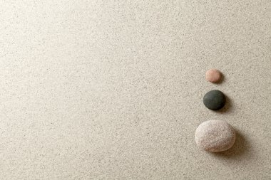 Three colorful zen stones at right side of sand background stock vector