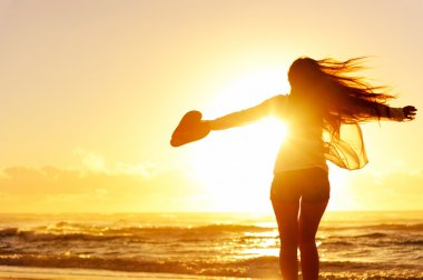 Carefree woman dancing in the sunset
