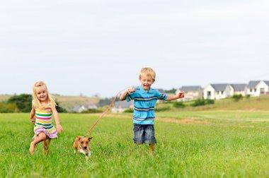Cute blond kids running in a field