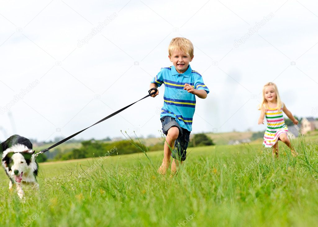 Happy children running outdoors with dog