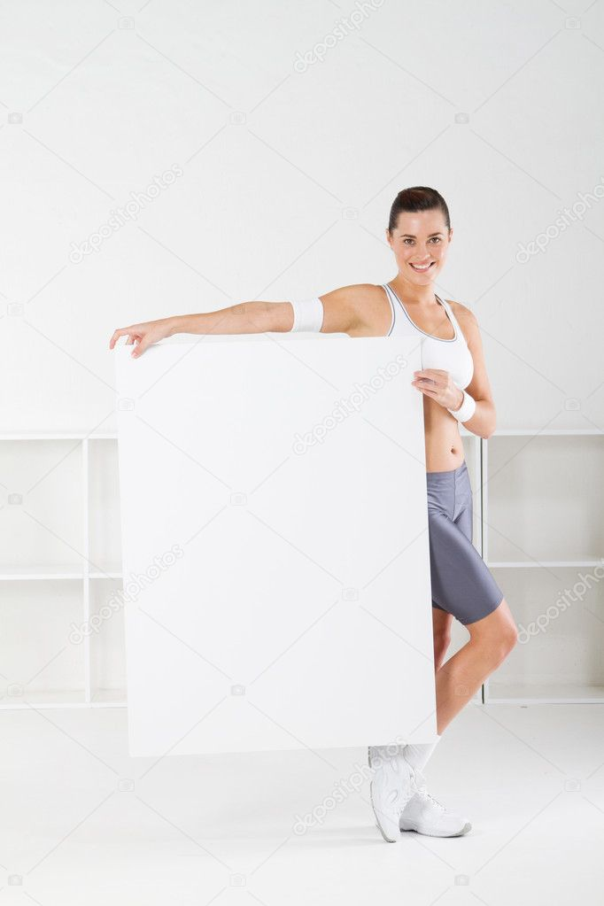 Cute young fitness woman holding a white board