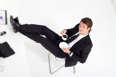 Young businessman drinking coffee in office
