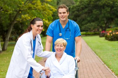 Caring medical doctor, nurse and senior patient outdoors