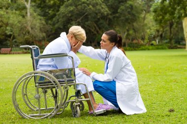 Young doctor comforting a lonely disabled senior patient outdoors