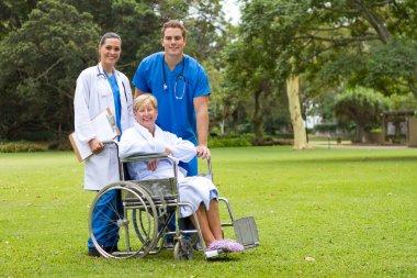 Group portrait of doctor, nurse and senior patient in hospital garden