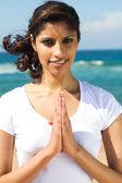 junge glückliche indische Frau betet am Strand