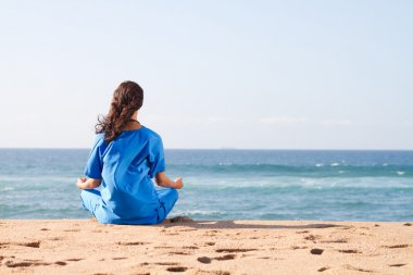Young nurse meditation on beach
