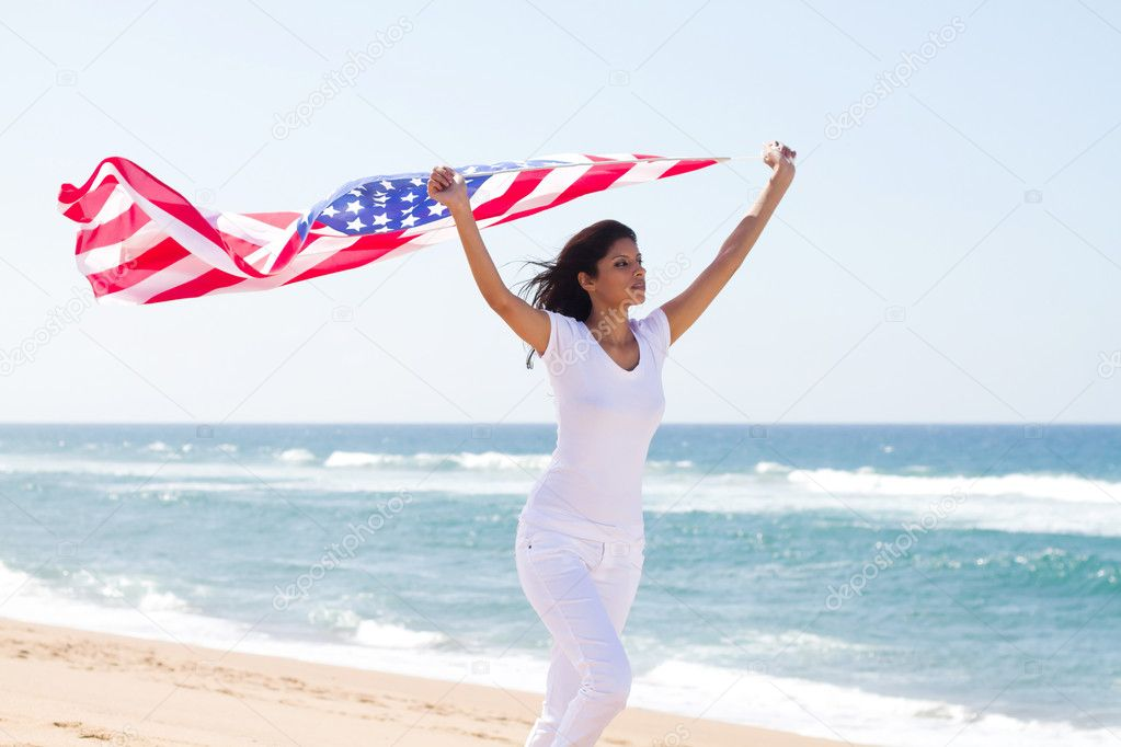 Woman holding american flag and running on beach