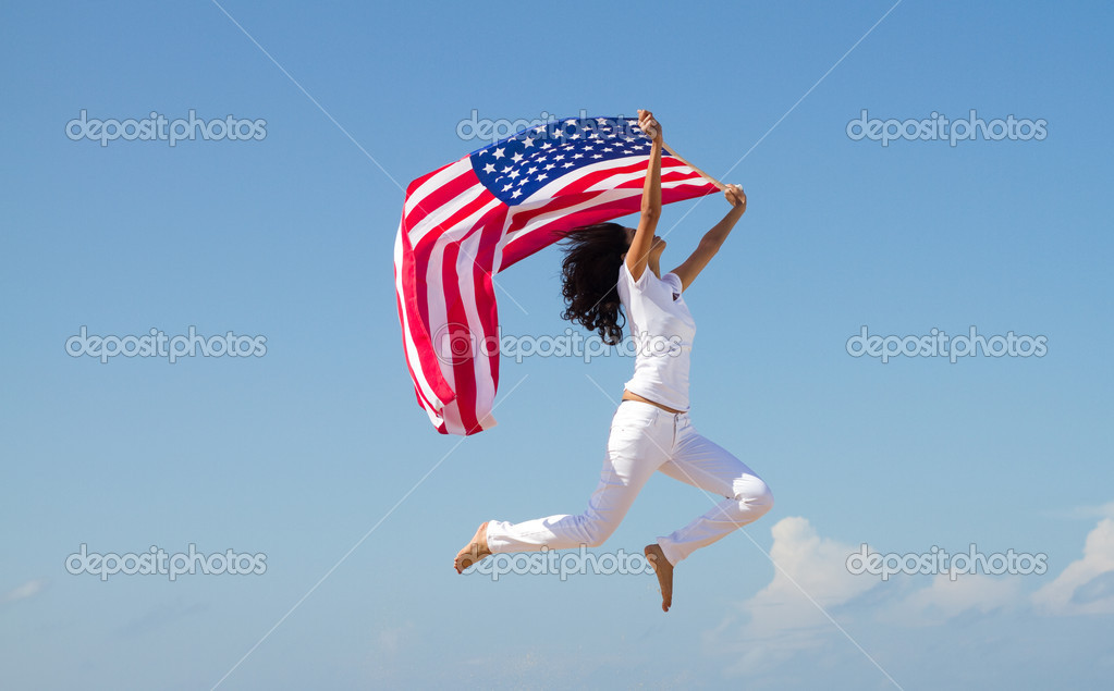 Young active woman with american flag and jumping