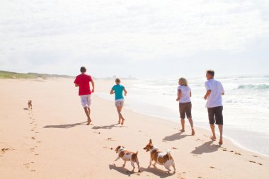 Active happy family with dogs running on beach