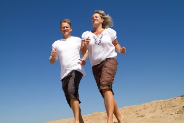 Middle aged couple running on beach