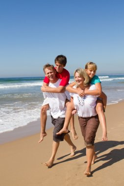 Happy family piggyback on beach