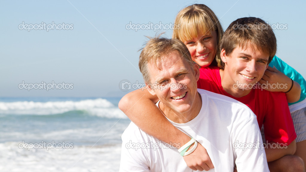 Middle aged father and teen kids on beach