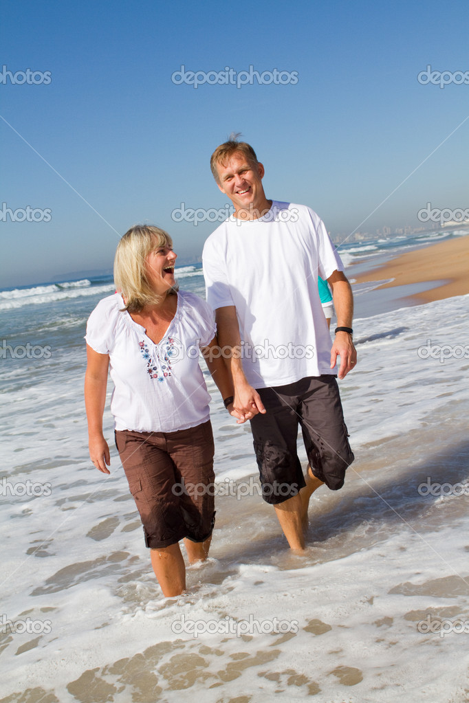 Middle aged couple walking on beach