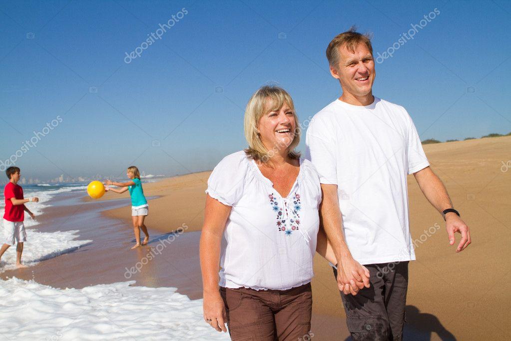 Happy mid age couple teen kids walking on beach