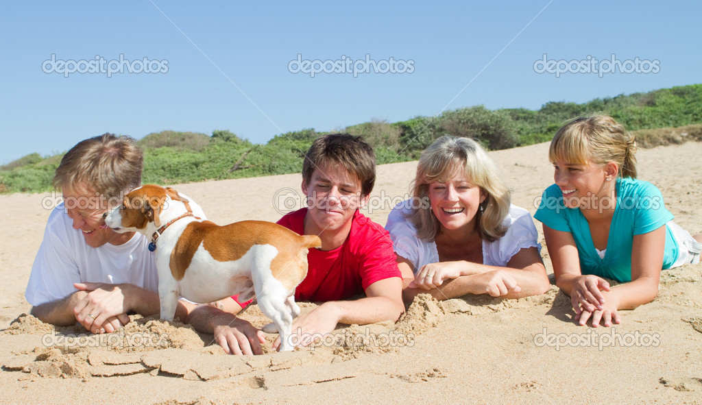 Family with pet dog lying on beach