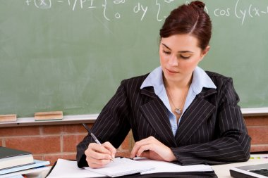 Female school teacher preparing lesson in classroom