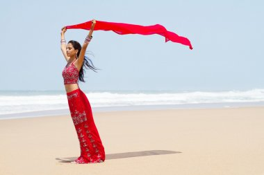 Indian woman holding sari on windy beach