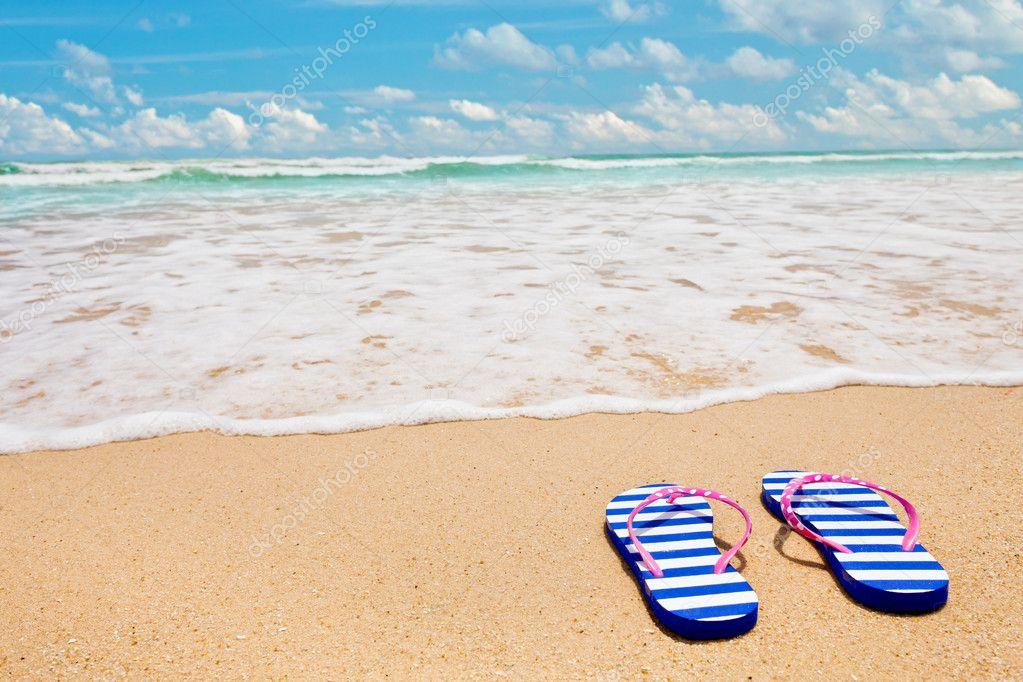 2fdfd06fd Colorful striped sandals on sea beach — Stock Photo © Andrey Kuzmin ...
