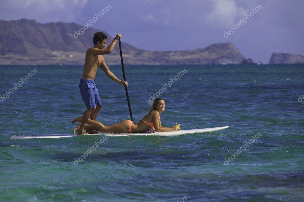Couple on standup paddle board in hawaii