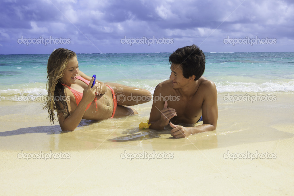 Couple on the beach in hawaii with their cell phone