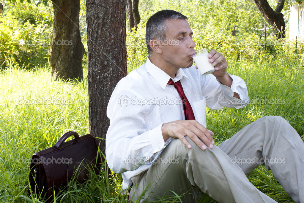 Businessman drinks fresh milk upon nature