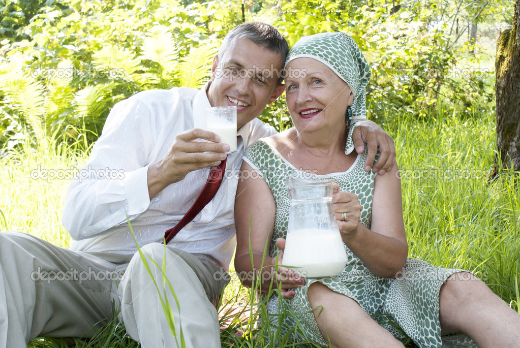 Happy femaly drinks pair milk in a summer gard