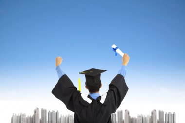 Successful graduating student with sky background
