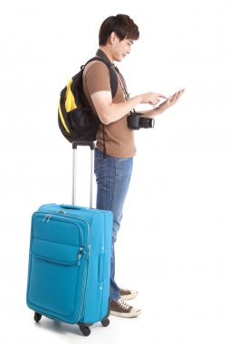 Full length of young traveler using tablet pc