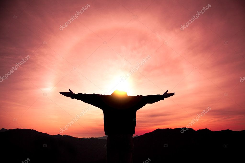 Man standing on the top of mountain and watching the sunrise