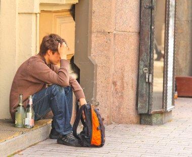 Sad drunk man sitting alone on sidewalk