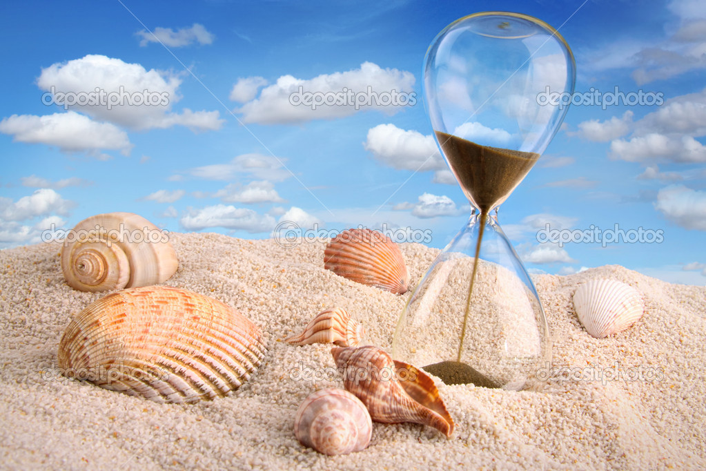 Hourglass in the sand with blue sky