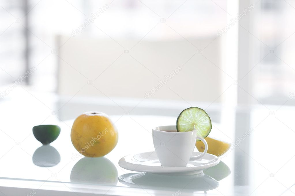 Cup of tea with tropical fruits on a glass surface