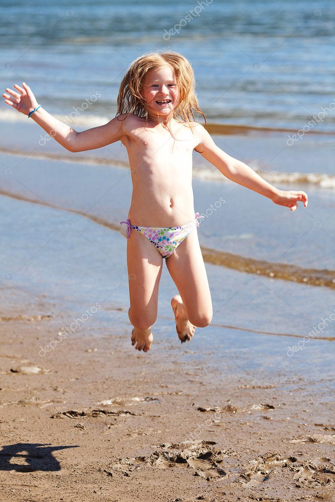 Beautiful little girl jumping on the beach