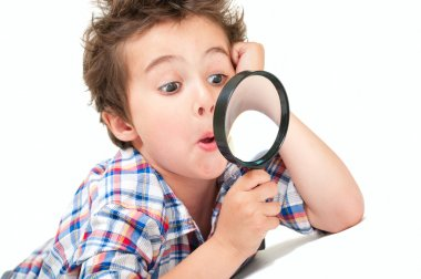 Surprised little boy with weird hair and magnifier