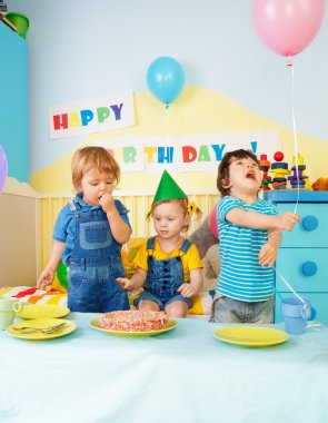 Three kids eating birthday cake