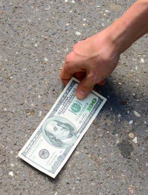 Hand picking money from street floor - Finding money on street c