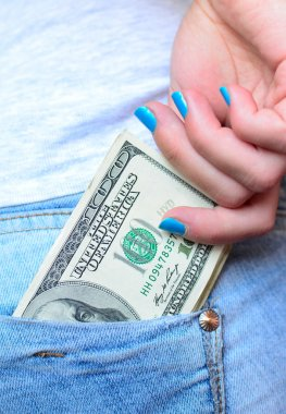 Woman hand taking money from jeans back pocket