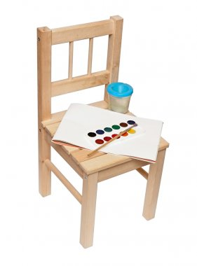 A little wooden chair with paints and brushes to paint isolated