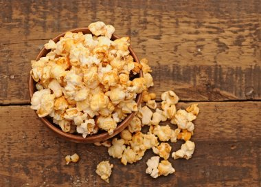 Popcorn in wooden bowl on wooden table